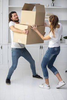 Couple with girlfriend carrying cardboard boxes in new home - ERRF00757