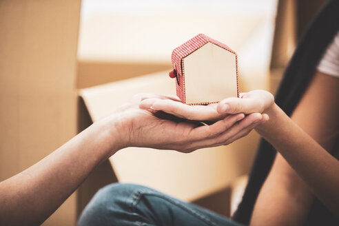 Close-up of couple holding tiny house model - ERRF00763
