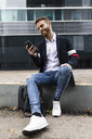 Stylish businessman sitting in the city using cell phone - JRFF02587