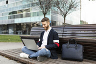 Stylish businessman sitting on bench in the city using laptop - JRFF02596