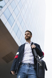 Stylish businessman in front of office building looking around - JRFF02608