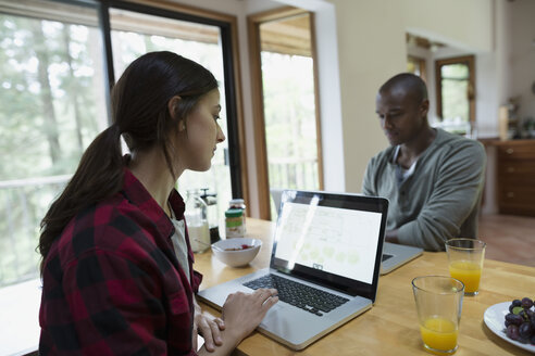 Couple using laptops face to face at breakfast table - HEROF18410