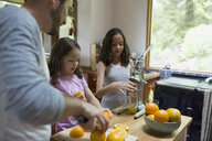 Father and daughters juicing oranges in kitchen - HEROF18419