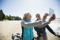 Couple with bicycles taking selfie with digital tablet camera on sunny beach - HEROF18449