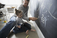 Father and daughter drawing on blackboard wall - HEROF18503