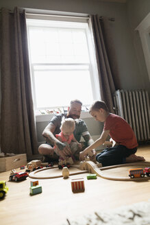 Father and children playing with toy train on floor - HEROF18542