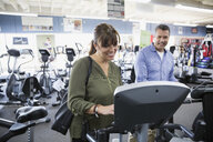 Couple browsing cardio machines at home gym equipment store - HEROF18587