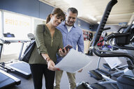 Couple browsing information sign on cardio machine at home gym equipment store - HEROF18590