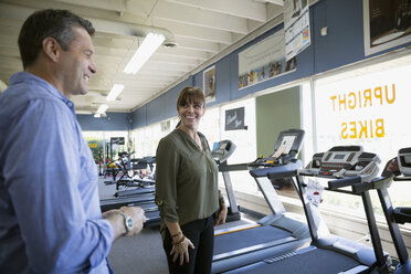 Couple browsing treadmills in home gym equipment store - HEROF18593
