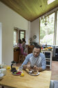 Father using cell phone at kitchen table while daughters do dishes in kitchen - HEROF18605