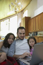 Father and daughters watching video on laptop on living room sofa - HEROF18608