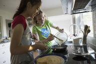 Girls making pancakes in kitchen - HEROF18698