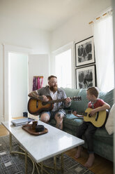 Father teaching son playing guitar in living room - HEROF18746