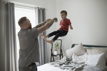 Father throwing son onto bed - HEROF18755