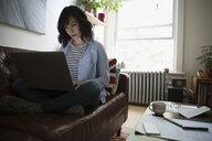 Female architect using laptop on living room sofa - HEROF18773