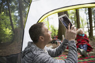 Man using digital tablet camera inside camping tent - HEROF18806
