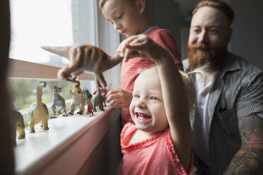 Happy father and children playing with toy dinosaurs at windowsill - HEROF18920