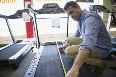 Man measuring treadmill at home gym equipment store - HEROF18977