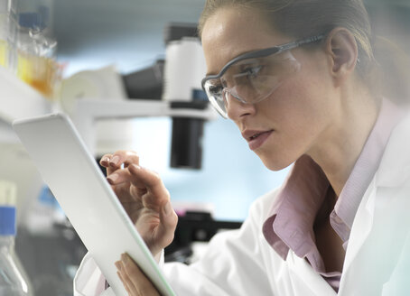 Scientist adding data to a tablet during an experiment in the laboratory - ABRF00299