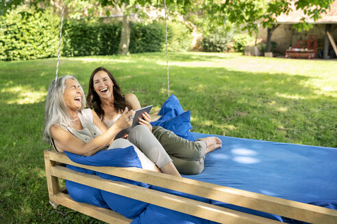 Two laughing women relaxing on a hanging bed in garden using tablet - PESF01269