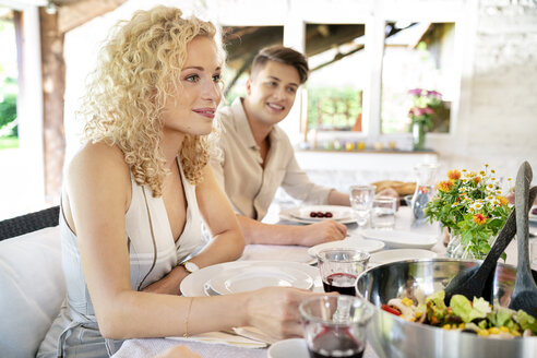 Smiling young woman having meal with family - PESF01275