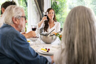 Portrait of smiling woman raising her wine glass on a family celebration - PESF01278