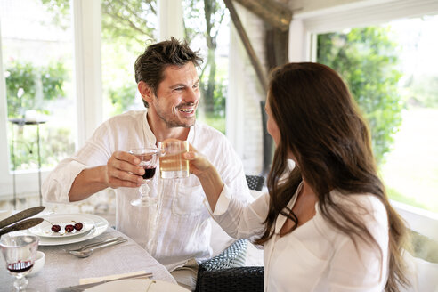 Happy couple clinking glasses at dining table - PESF01284