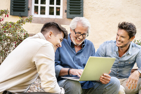 Three happy men of different age using laptop in garden - PESF01296