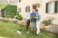 Three men of different age standing in garden using tablet - PESF01299