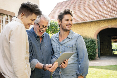 Three happy men of different age using tablet in garden - PESF01302