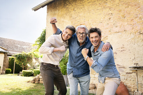 Portrait of three excited men of different age embracing and cheering in garden - PESF01305