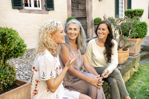 Three happy women of different age sitting at country house talking - PESF01308