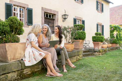 Three happy women of different age sitting in garden using tablet - PESF01311