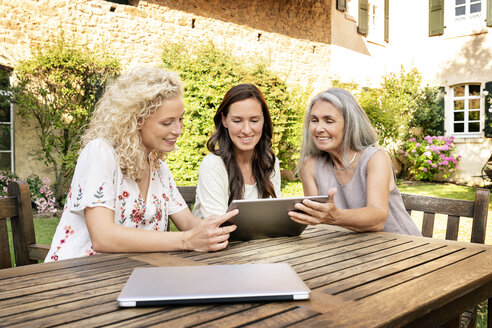 Three women of different age sitting at garden table using tablet - PESF01314