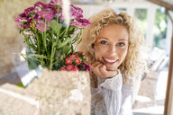 Portrait of smiling young woman with flowers - PESF01335