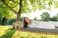 Mature woman relaxing on a hanging bed in garden - PESF01338