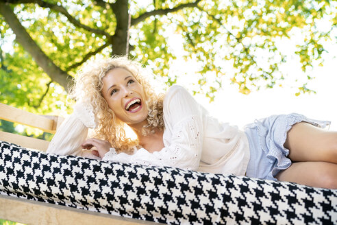 Happy young woman lying on a bed in garden - PESF01344