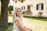 Portrait of smiling woman with long grey hair in garden - PESF01347