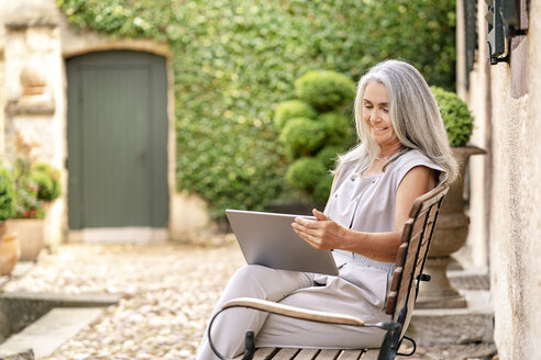 Woman with long grey hair sitting on bench at country house using tablet - PESF01353