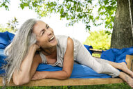 Laughing woman with long grey hair lying on a bed in garden - PESF01368