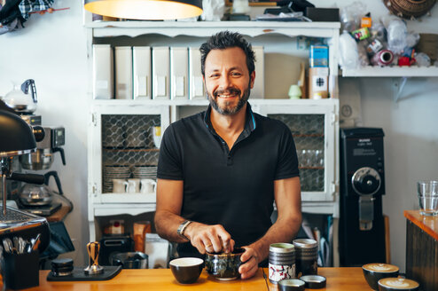 Portrait of smiling barista at the counter of a coffee shop - OCMF00270