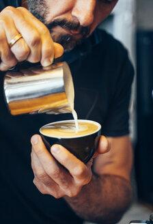 Barista waiter working in coffee shop. Prepare decorated coffees. - OCMF00273