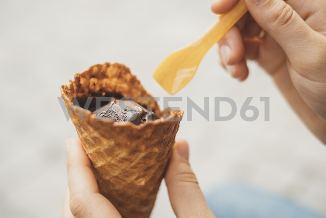 Woman's hand holding ice cream cone with cholocolate ice, close-up - JSCF00135