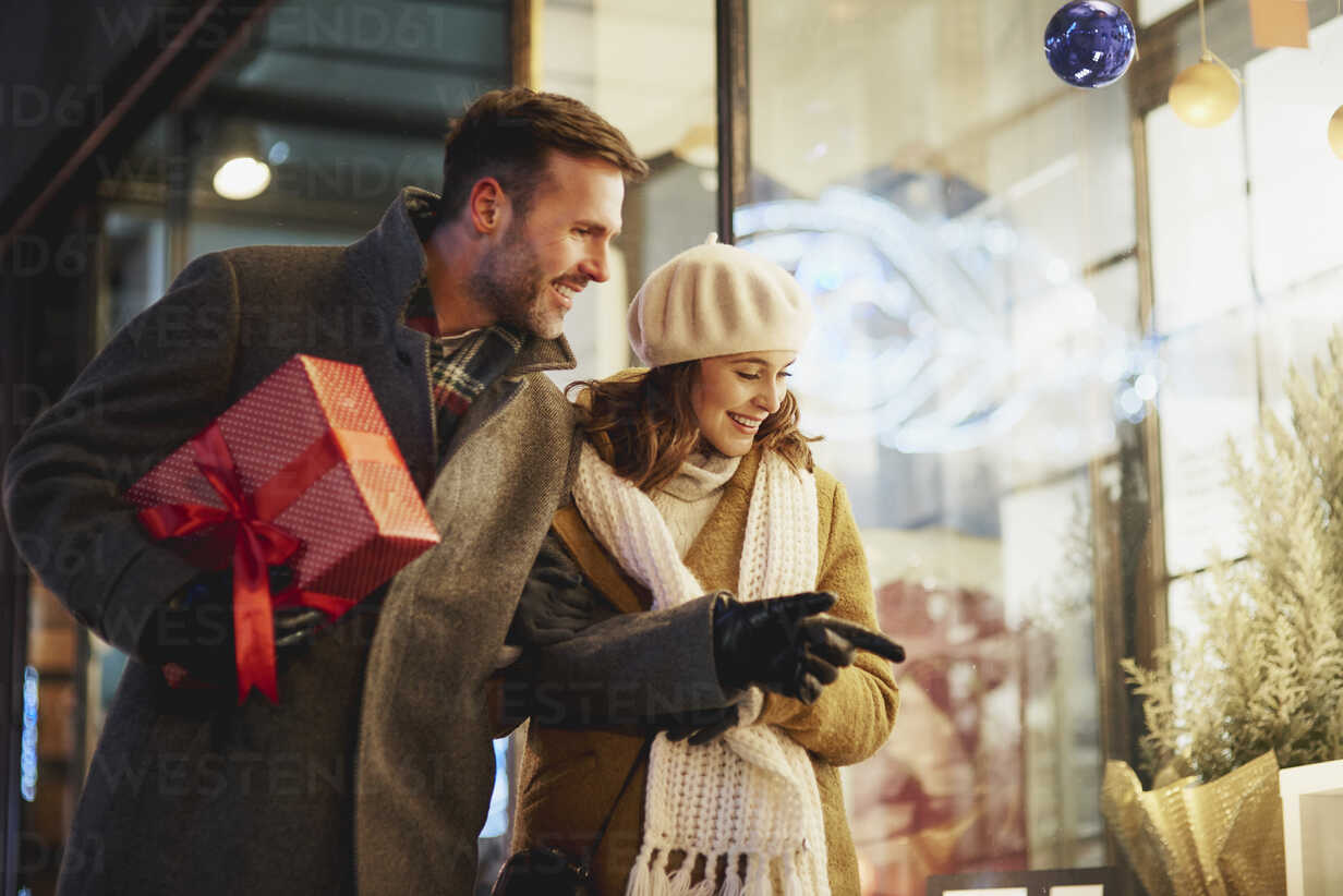 Smiling couple looking in shop window at Christmas time - ABIF01153 - gpointstudio/Westend61