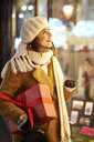 Smiling woman with Christmas present looking in shop window - ABIF01156