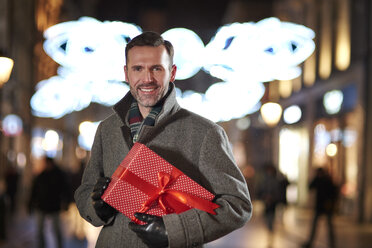 Portrait of smiling man with Christmas present looking at pedestrian area in the evening - ABIF01159