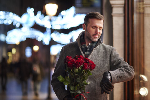 Portrait of waiting man with bunch of red roses checking the time - ABIF01162