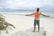 South Africa, man raising arms at Bloubergstrand - ECPF00372