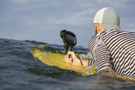Indonesia, Bali, man with waterproof smartphone in the sea - KNTF02641