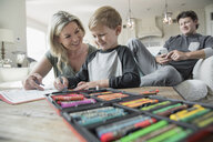 Mother and son coloring in living room - HEROF19022